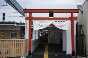A red tori stands at the entrance of Fujikyuko Railway Station, and there are lockers available
