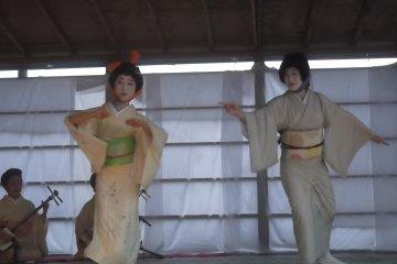 <p>Гейшы танцуют коимчный танец на открытой сцене; оранжевая повязка делает одну гейшу тыквой, другая изображает баклажан.</p>