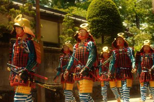 Impressive blue and red samurai warriors in lamellar armor andgold-colored kabuto helmets are an example traditional dress displayed during the procession.