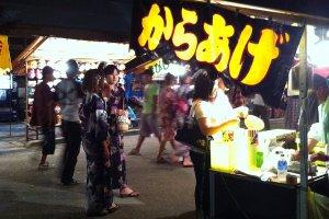 Girls wearing yukata check out the stalls