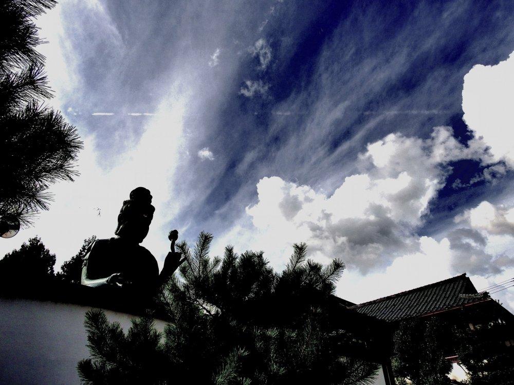 Fukui Daibutsu với ánh mặt trời trên lưng dưới bầu trời xanh với những vệt mây trắng