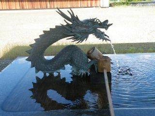 Une fontaine pour la purification à l'entrée de la statue Kannon