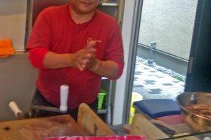 Satu dari dua koki sedang mempersiapkan kerupuk gurita segar