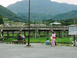 A côté de la rivière Katsura, les touristes locaux se détendent et profitent des après-midis d'été. Togetsukyo, en arrière-plan, est l'un des célèbres ponts d'Arashiyama
