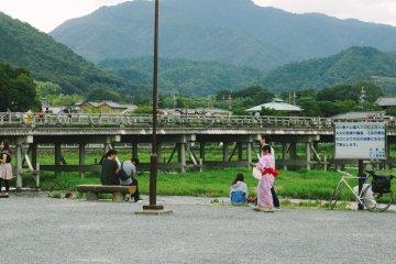 Al pasar por el río Katsura, los turistas se relajan y disfrutan de la tarde de verano. Togetsukyo, al fondo, es uno de los puentes famosos de Arashimaya