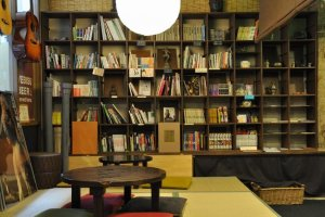 Ugaya Guesthouse's common area is stocked with books, souvenirs, and maps.