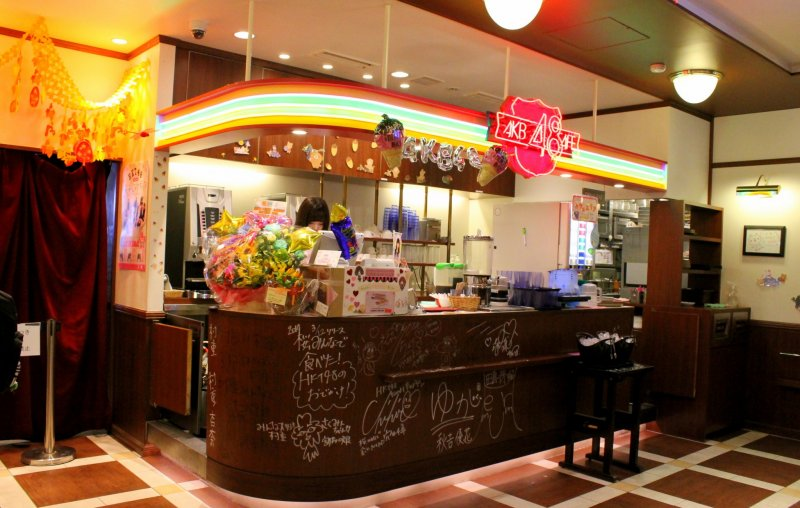 <p>The colorful counter in the cafe is covered with autographs of the AKB48 members</p>