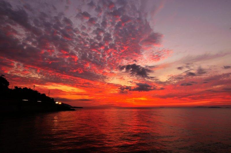 <p>เมื่อพระอาทิตย์ตกที่ขอบฟ้า ท้องฟ้าและน้ำทะเลเป็นสีแดงฉาน</p>