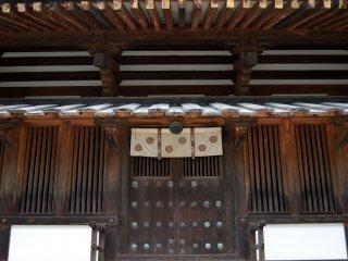 Деревянная дверь с красивыми узорами. Это один из входов в пятиярусную пагоду храма