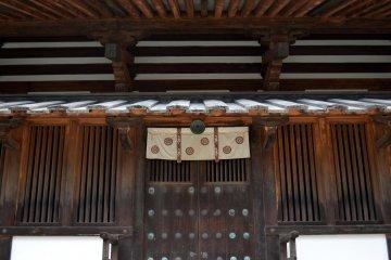 <p>아름다운 무늬가 그려져 있는 나무 문. 이 문은 절의 5층탑으로 올라가는 입구들 중 하나다.</p>