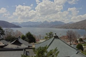Over the black tiled roof of the temple buildings, you can see Chuzen-ji Lake and the elegant lower south slope of Mt. Nantai.