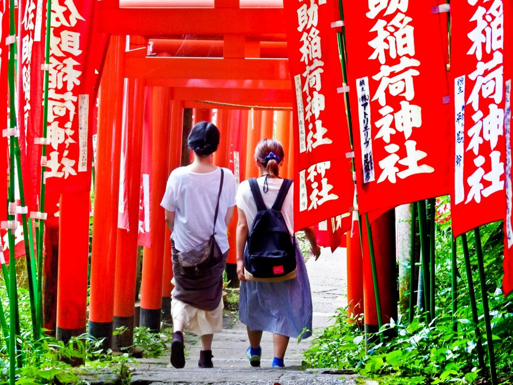 Two visitors gradually disappearing into a thick sea of red torii (gates)