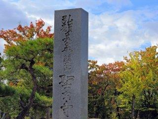 美しい初秋の紅葉を背景に建つ聖玄寺の石柱