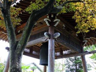鐘楼の美しい木彫り細工と色付き始めた紅葉