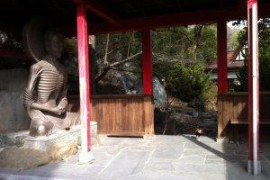 Skeletal Buddha and cockerel