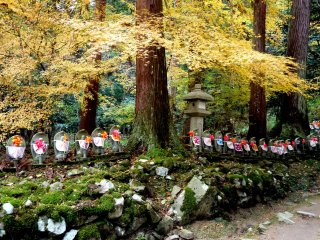 Yellow maple leaves spread over the statues like a golden blessing