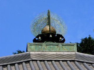 Intricate roof ornament against a clear blue sky