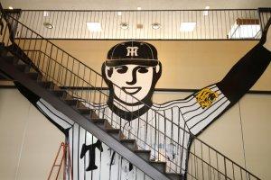 กูลิโกะแมนตัวยักษ์ที่เราจะเจอต้อนรับเป็นด่านแรก ซึ่งกูลิโกะแมนตัวนี้สวมชุดลายทางขาวดำอันเป็นชุดเบสบอลของทีม Hanshin Tigers ที่โด่งดังเลื่องชื่อแห่ง จ.เฮียวโกะ ซึ่งทางกูลิโกะก็เป็นสปอนเซอร์ให้ทีมนี้ด้วย โดยกูลิโกะแมนในชุดเบสบอลตัวนี้เป็นตัวเดียวกับที่เคยถูกนำขึ้นไปติดตั้งที่ป้ายนีออนชื่อดังแห่งโดตนโบริในโอกาสพิเศษเมื่อปี ค.ศ.2003