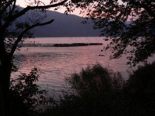 Le ciel rose se reflète à la surface de l'eau
