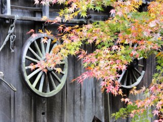 An old wheel hangs on the side of one of the thatched roof homes