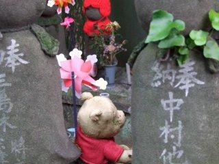 Pequeños juguetes y animales de peluche (como este oso Pooh) a menudo se dejan en la base de la estatua