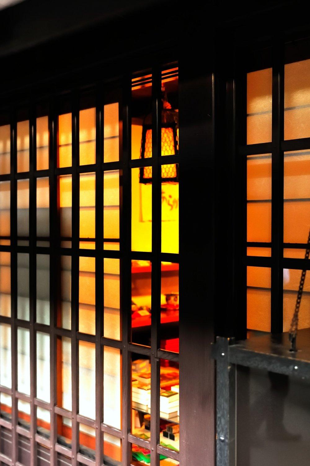 古い街並み、三之町を歩く。土産物屋の格子窓から温かな灯りが漏れている