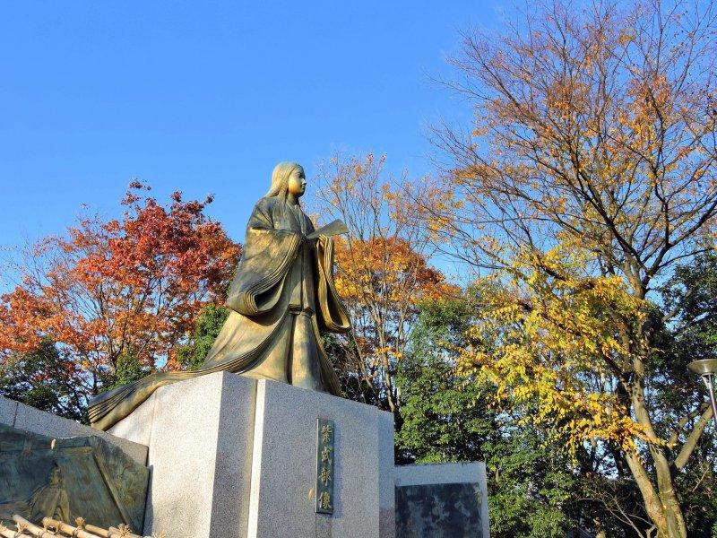 가을 낙엽과 푸른 하늘과 뚜렷한 대비를 이루는 금으로 만든 무라사키 시키부 동상