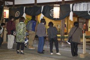 La veille du festival, les habitants viennent admirer le dieu et les décorations de la salle qui l'abrite