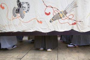 Des chanteurs et musiciens cachés sous lesiori-yatai, on ne voit que les pieds chaussés de geta