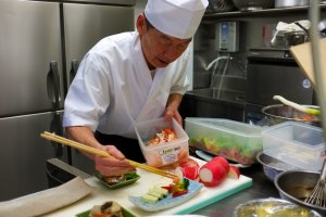 One of the chefs prepares dishes in the kitchen