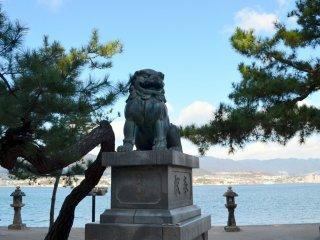 Sebuah patung anjing penjaga dengan bagian belakangnya yang menghadap ke laut.