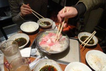 <p>Diners cluster around a pot of Kagoshima&#39;s black pork shabu shabu</p>