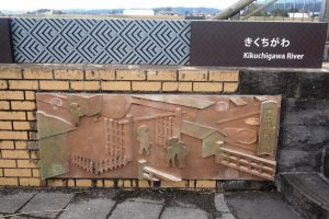 A relief showing rice merchants at the riverbank entrance to the Buzen Way