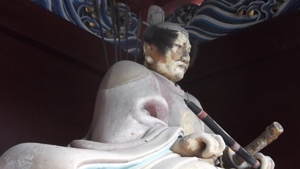 Uma estátua de guarda num dos portões do santuário