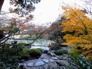 Caminho de pedras debaixo de folhas amarelas junto ao lago do jardim