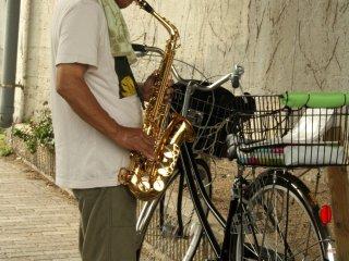 A buskerperforming on his saxophone near Toji Shrine