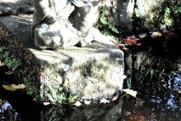 รูปปั้นนั่งอยูในสระน้ำเล็กๆ ของวัด