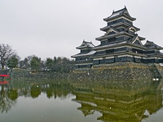 Snow covered roof tops (and two swans!) at Matsumoto Castle. One of four National Treasures in Japan.