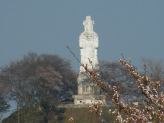 The Kannon overlooking the tree-lined river