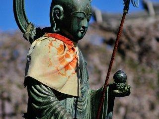 Patung jizo yang berdiri di depan ruang utama sedang menyampaikan rasa kasihnya