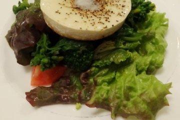 <p>Warm camembert cheese tops a salad of fresh greens</p>