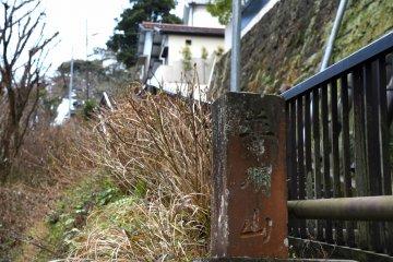 죠쥬인의 오래되고 구부러진 돌 표지는 사찰로 이어지는 돌 계단에 서 있다