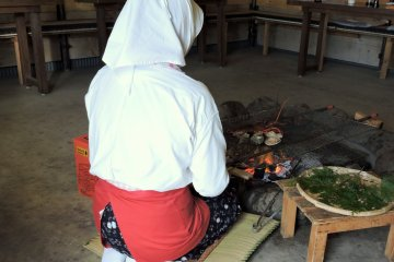 <p>Costumed Ama diver cooking lunch in the Ama hut</p>