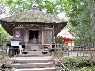 Visitors pray to Fudo Myo-o, the protector of Buddhism and one of the Wisdom Kings, at this thatched roof sub-temple building.