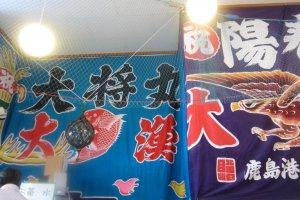 Bendera 'tangkapan besar' lebar dari berbagai pelabuhan menghiasi tembok