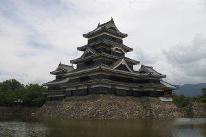 """Из-за черных стен и характерного очертания боковых башен, напоминающих распростертые птичьи крылья, замок Мацумото был прозван """"Замком черного ворона"""""""