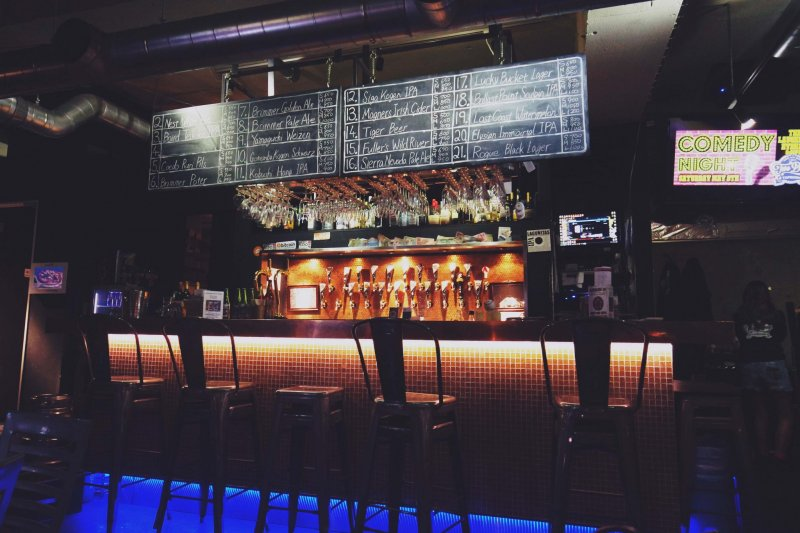 <p>The bar glows with neon lights and warm colors inside Two Dogs.&nbsp;</p>