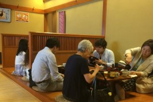The tatami-matted dining area features large wooden tables with wells for comfortable seating.