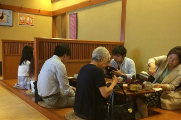 <p>The tatami-matted dining area features large wooden tables with wells for comfortable seating.</p>