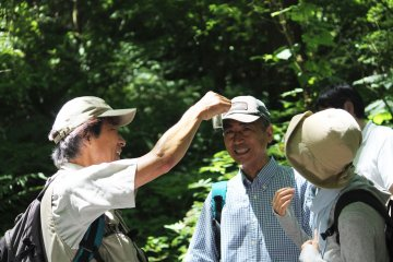 <p>Our guide shows us a tadpole from the nearby pond</p>